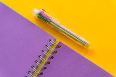 Carnet pourpre de stylo pourpre sur le fond jaune image stock