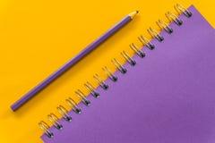 Carnet pourpre de stylo pourpre sur le fond jaune photo libre de droits