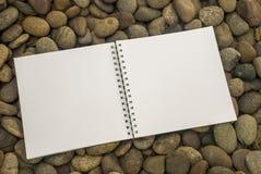 Carnet qui est placé sur une pile des pierres image stock