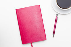 Carnet rose avec le stylo et une tasse de café noir sur le blanc Photo libre de droits