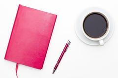 Carnet rose avec le stylo et une tasse de café noir sur le fond blanc Photos libres de droits