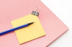 Carnet rouge avec le stylo bleu d'agrafe de post-it et de bouledogue d'isolement dessus Photographie stock libre de droits