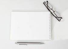 Carnet, stylo et verres sur la table Photos libres de droits