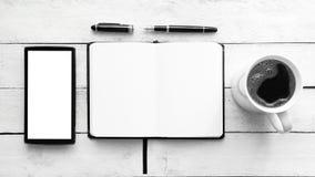 Carnet sur une table en bois blanche à côté d'un mobile, d'un stylo et de café dans une tasse Vue supérieure et espace vide de co Image stock