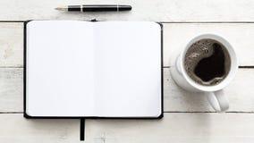 Carnet sur une table en bois blanche à côté d'un stylo et du café dans une tasse Vue supérieure et espace vide de copie Photos libres de droits