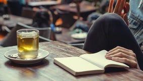 Carnet vert de page blanc de thé et avec les mains femelles sur une table en bois Photo stock