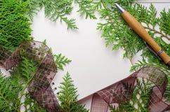 Carnet vide avec des feuilles de vert et stylo sur la table en bois Photo stock