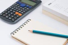 Carnet vide avec la calculatrice et le crayon sur le fond blanc Photographie stock libre de droits
