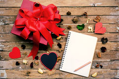 Carnet vide avec le boîte-cadeau rouge sur la table en bois et le flowe sec Photographie stock