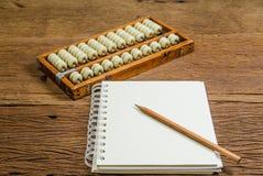 Carnet vide avec le crayon et l'abaque sur la table en bois Photographie stock libre de droits