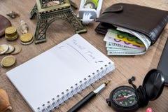 carnet vide avec le crayon, l'euro et le dollar dans le portefeuille, boussole, coquillage, téléphone, Tour Eiffel Photos libres de droits
