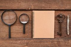 Carnet vide avec le crayon, la clé et la loupe Image libre de droits