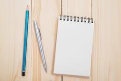 Carnet vide avec le stylo et crayon sur la table en bois Photographie stock