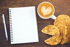 Carnet vide avec le stylo et les biscuits chauds de café Images stock