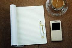 Carnet vide avec le stylo futé de téléphone et tasse de café sur la table en bois, concept d'affaires Photographie stock