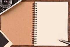 Carnet vide avec le stylo, les cadres de photo et l'appareil-photo Photographie stock