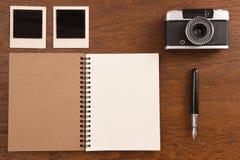 Carnet vide avec le stylo, les cadres de photo et l'appareil-photo Photographie stock libre de droits