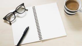 Carnet vide avec les lunettes, le stylo et la tasse de vintage de café chaud sur la table en bois Photos libres de droits