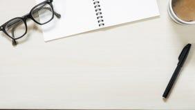 Carnet vide avec les lunettes, le stylo et la tasse de vintage de café chaud sur la table en bois Photo libre de droits