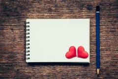 Carnet vide et coeur rouge avec le crayon sur le fond en bois Photo libre de droits