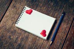 Carnet vide et coeur rouge avec le crayon sur le fond en bois Photo stock