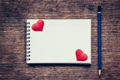 Carnet vide et coeur rouge avec le crayon sur le fond en bois avec Image libre de droits