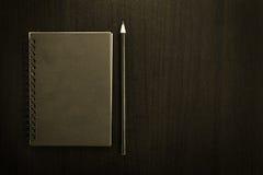Carnet vide noir avec le crayon sur le fond foncé de tableau Photos libres de droits