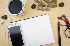 Carnet vide ouvert avec le smartphone, le stylo et la tasse de café Photos stock