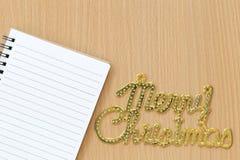 Carnet vide placé près du texte de Joyeux Noël sur W brun Photographie stock