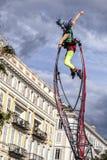 Carnevale di Nizza, battaglia del ` dei fiori Una donna dell'acrobata con il costume del pagliaccio sul fondo del cielo Fotografia Stock