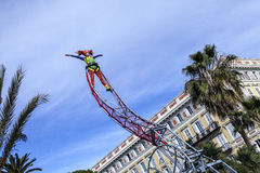 Carnevale famoso di Nizza, battaglia del ` dei fiori Una donna dell'acrobata con il costume del pagliaccio sul fondo del cielo Fotografia Stock Libera da Diritti