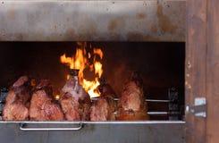 Carni affumicate sulla griglia al mercato di Natale Fotografie Stock Libere da Diritti