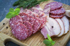 Carni - salame, bacon e verdi su un tagliere Fotografia Stock Libera da Diritti
