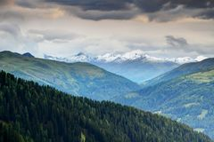 Carnic and Gailtal Alps pine forests and morning snow in Tauern. Green pine forests of Carnic and Gailtal Alps slopes in Obertilliach Lesachtal valley in summer Royalty Free Stock Image