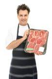 Carniceiro com a bandeja de bife foto de stock