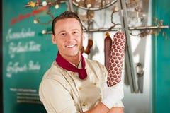 Carniceiro com a salsicha fumada fresca Imagem de Stock