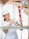 Carniceiro Cutting Sausages At que vende contra Fotos de Stock