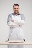 Carniceiro de sorriso que está atrás da tabela. foto de stock royalty free