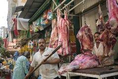 Carniceiro e carne fresca na frente de seu negócio imagens de stock royalty free