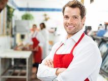 Carniceiro feliz Standing Arms Crossed na loja Foto de Stock