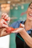 Carniceiro fêmea que vende a carne fresca ao cliente Imagens de Stock Royalty Free