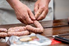 Carniceiro que faz salsichas na fábrica da carne imagem de stock