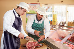 Carniceiro Teaching Apprentice How para preparar a carne fotografia de stock