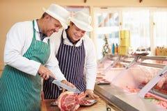 Carniceiro Teaching Apprentice How para preparar a carne Imagem de Stock