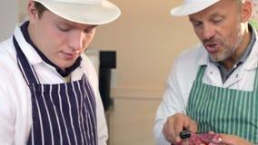 Carniceiro Teaching Apprentice How para preparar a carne vídeos de arquivo