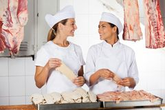 Carniceiros fêmeas que guardam a carne crua no contador Fotos de Stock Royalty Free