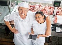 Carniceiros felizes com a tabuleta de Digitas no açougue Fotos de Stock Royalty Free