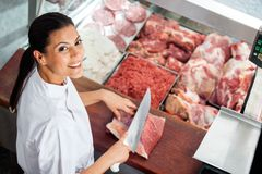 Carnicería femenina feliz de Cutting Meat At del carnicero Foto de archivo