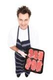Carnicero con la carne fresca Imagen de archivo