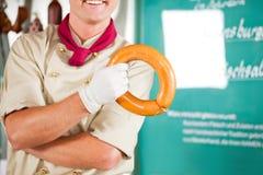 Carnicero con la salchicha fresca en el departamento Imagen de archivo